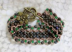 """Deb Roberti's ribbon bracelet.  11/0 duracoat galvanized light golden brown, 4 mm fp matte brown iris, 3 mm fp green grass.  These green beads are the ONE green my daughter said she liked in the bead store and they had only the 3 mm.  I am not sure they are really the """"green grass"""" as they are slightly occluded- but my searches on the interwebs have not pulled up a direct match to them.  Ben Franklin is having a fp trunk show in two weeks so I'll try there.  I think I'll change the toggle…"""