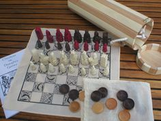 Portable chess set with fabric board, Isle of Lewis pieces and wooden carrying tube.
