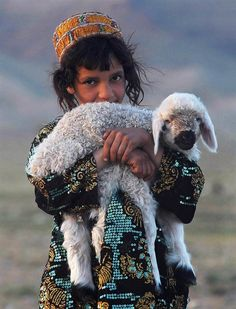 A girl holds a lamb on the outskirts of Herat on April 10.
