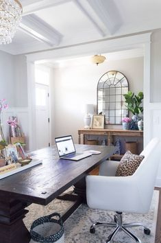 Chic and girly home office with farmhouse trestle table, DIY Gold chandelier, vintage rug, arched mirror