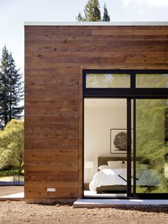 The modestly scaled master bedroom opens to a view of the woods located behind the property.  Photo by: Matthew Millman