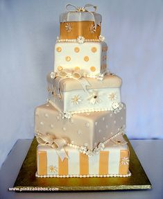 Unique box themed mulit tiered wedding cake with delicate details in a palette of gold, sliver, ivory and bronze