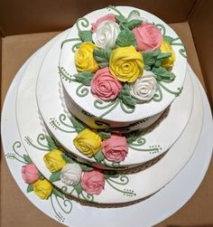 White, pink and yellow roses are beautiful on the three tier wedding cake