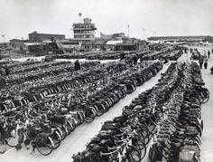 Bromfietsen/snorfietsen. Ruim 3000 bromfiets bezitters uit alle delen van het   land komen op Schiphol bijeen om een rally rond de luchthaven te rijden om op   deze manier het lawaai van de vliegtuigen te overstemmen. Datum onbekend,   vermoedelijk jaren '60. Op de achtergrond de verkeerstoren van het ' oude    Schiphol.