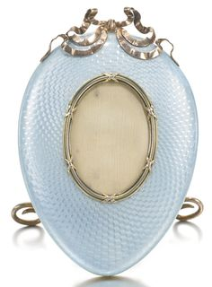 An Imperial Fabergé silver-gilt and enamel frame, workmaster Anders Nevalainen, St Petersburg, circa 1895. Of egg form, the surface of translucent powder blue enamel over radiating engine-turned waves, the oval aperture with bound reed bezel, ribbon tie surmount. Purchased by Empress Alexandra Feodorovna for 68 rubles in 1911.