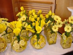 Lemons in water...fun, fun, fun summer table decorations.  You could put any color flower or peacock feathers inside the vases.