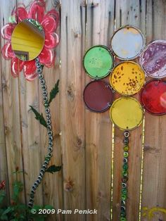 """Fence flowers made from paint can lids, bottle caps and mirrors."""
