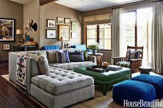 """The family room is sports central,"" designer Nathan Turner says of client Eric Stonestreet's Los Angeles house. A custom sectional in Calvin Fabrics' Antiquity faces an enormous flat-screen television. The Candemir ottoman from Nathan Turner, covered in Elite leather, is tough enough to handle football fans with their feet up, and an original Gustav Stickley armchair strikes a masculine note. Bubble Knit poufs, West Elm. Curtain and shade in William Yeoward's Padstow. - HouseBeautiful.com"