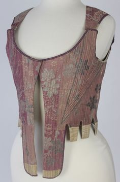 18th Century Metallic Brocade Stays, French c. 1750 Deaccessioned from the Metropolitan Museum of Art. Constructed from plum silk with pink and metallic floral brocade. Decorated in a wonderful narrow metallic braid. The waist tabs are elongated at the center front and there are hidden eyelets in linen lining. Condition is very good to excellent! Minor wear and soiling (normal for almost 300 years old) some tabs ends have been replaced (along time ago). Measurements: Bust: 34 inches (86 cm)…