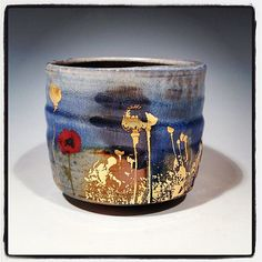 cup with gold poppies and blue glaze by justin rothshank. Fired in a wood/soda kiln.