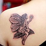 Fairy tattoo on a girl's shoulder- hmm to cover Tink? then build with flowers onto shoulder?