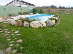 piscina con perímetro de rocas y  flores