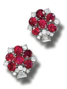 PAIR OF RUBY AND DIAMOND EARCLIPS, BULGARI.  Each flowerhead motif set with oval rubies, accented by brilliant-cut and baguette diamonds, mounted in white gold,  signed Bulgari, fitted case.