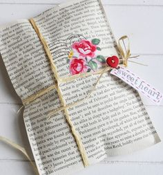 Sweet gift packet….made from pages of an old book decorated with rubber stamps, flowers cut from rosy fabric or paper and tied up with raffia and add a heart button and tag ❥ @ Do It Yourself Pins