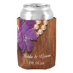 Personalize the Purple Periwinkle and Pearls Country #Wedding Can Cooler with names of the bride and groom and marriage date to create a wedding, shower or party favors. This shabby chic custom wedding can cooler features a quaint floral photograph of purple flowers and pearl necklace with a brown barn wood background. Perfect for the cold beverages at the reception of your casual yet classy rural country farm, rustic barn, ranch or western wedding theme. #barnwedding #weddingfavors #koozies