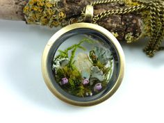 Romantic terrarium locket featuring a tiny fairy garden with a colourful mix of mosses, lichens and a raw, yet shimmering opal shining out