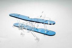 Avião em miniatura feito de acrílico cristal e acrílico azul translúcido ref. AZ-508 4mm, e avião preto 3mm com detalhes de acrílico cristal, aplicados os processos de corte a laser, montagem e colagem.