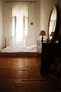 Schlichte Einrichtungsidee für einen romantischen WG-Zimmer-Traum: Offene Spitzengardine, Matratze mit flauschiger Bettdecke, Holzdielenboden, hölzerne Kommode mit Goldrandspiegel. WG-Zimmer in Berlin. #Berlin #room #flatshare