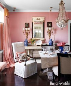 Jane Austen-inspired ballgown curtains and matching silk blend on the walls — Vervain's Caserta Satin — give designer Kelee Katillac's Kansas City dining room its romantic, rose-quartz flush. An antique Breton armchair, slipcovered in linen cut from a vintage tablecloth, stands out like a white rose. Below the chair rail, Kravet's Velvet Gate anchors the room.   - HouseBeautiful.com