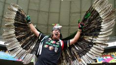 A Mexico fan poses with feathered wings
