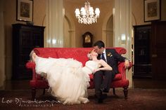 Another great red couch shot Bride and groom kissing on red antique sofa. The Tidewater Inn Wedding, Easton Maryland, reception photo coverage of Kelsey and Jonnie by wedding photographers of Leo Dj Photography.