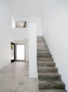 Escaliers en béton - Concrete stairs in a white home.