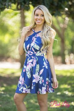 This lovely floral dress is perfect for all of your spring occasions! Featuring a large floral pattern in pink, lilac, light green, white, and grey on a navy blue fabric, these bold blooming hyacinths, orchids, and other flowers will really stand out! We adore the details on this dress as well - the low cut keyhole detail in front and halter back with a unique strap pattern in the back are so trendy!