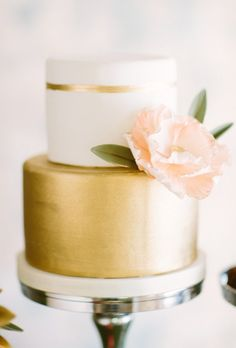 A two-tiered white-and-gold wedding cake with a gold striped accent, from Sugarbelle Cakes.
