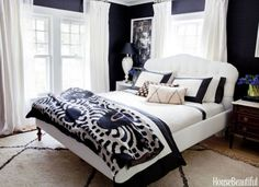 The master bedroom gets an urbane look thanks to dramatic ebony walls, Acacia Grass by Ralph Lauren Home, and an upholstered bed from ABC Carpet & Home. Modern Border duvet and shams by DwellStudio. Bara Cash mere throw by Madeline Weinrib. Curtains in Restoration Hardware's Belgian Textured linen.   - HouseBeautiful.com
