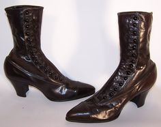 This pair of antique Victorian era women's black leather high top button boots date from 1900. They are made of a supple black leather, with decorative punch work trim across the front toes. The boots have pointed toes, 14 black shoe buttons along the side for closure and stacked wooden cube heels.
