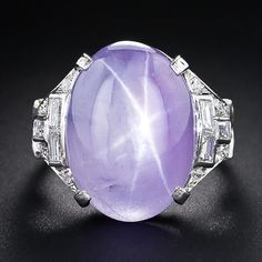 An enchanting and exotically colored lavender star sapphire, weighing 18.50 carats and fashioned by a masterful lapidary to present considerably larger, is presented in consummate and sophisticated Art Deco glory in this magnificent and unique gemstone and diamond ring, hand fabricated in platinum, circa 1930.