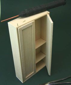 A brass 'nail' or pin is inserted through the case of a dolls house scale armoire for a hinge pin.
