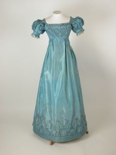 1820-25 ca. Blue Silk Gown.  High waisted bodice, wide square neckline, short sleeves with ruched fabric between vertical bands of fabric. Band around bottom with vandyked edge, lace frill inside. Neckline trimmed with twisted bands of fabric. Front bodice trimmed with applique of rouleaux. Lower skirt trimmed with overlapped applique triangles of fabric and self covered buttons. Four bands of quilting around on hem. Fastens at back with hooks and loops. nationaltrustcollections.org.uk