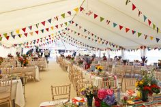 Beautiful beach themed marquee wedding. Flat ivory linings, champagne carpet and lots of colourful bunting!