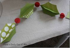 Cut out holly and berry shapes from double-sided cardstock. Sew two pieces of holly together then two pieces of berry, then holly etc. bend to make 3-D.
