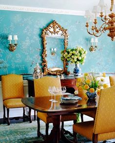 Turquoise dining room wallpaper with yellow chairs