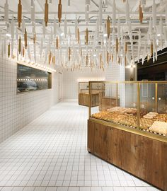 rolling pins hang from ceiling inside beijing bakery by B.L.U.E architecture studio
