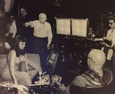 DeMille directs Anne Baxter and Sir Cedric Hardwicke (with glasses) on the set of The Ten Commandments