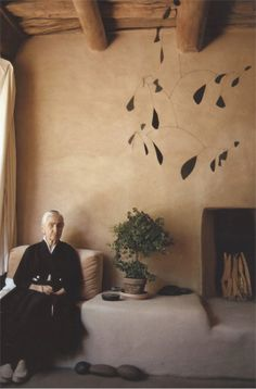 GEORGIA O'KEEFFE, Photographed at her Ghost Ranch home in Abiquiu, New Mexico, USA (c.1970s). The house was built in Adobe style, made out of straw and mud, which creates an unique soft and uneven surface on the walls. The hanging metal mobile was a gift from O'Keeffe´s friend, Alexander Calder (c.1940s). / The Red List