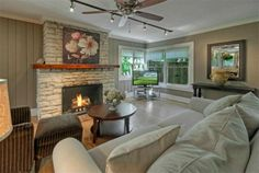 Spacious living room with white fireplace, natural lighting, and wood floors 2703 Bridle Path, Austin, TX 78703