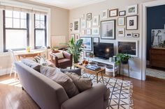 Emily's living room gallery wall is a Pinterest-worthy example of eclectic executed effectively and intentionally. The density helps the television blend into this focal area. The media stand is DIY.