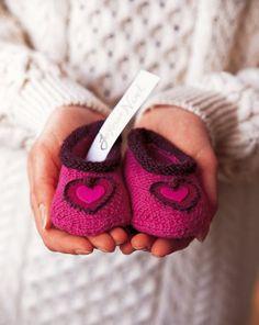 Chaussons tricotés en laine rose avec un petit cœur sur le dessus pour bébé