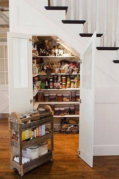 Der Raum unter der Treppe dient als einen Spaziergang in der Speisekammer. Ein paar Regale wurden installiert, um Lebensmittel-Container und Boxen zu halten. Ein kleines fahrbares Regal beherbergt einige Backen Bedürfnisse und kann beim Backen für den einfachen Zugriff herausgedrückt werden.
