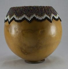 This lovely tall beaded gourd bowl or vase has been left natural color but sealed completely with clear acrylic spray.  The holes are drilled in