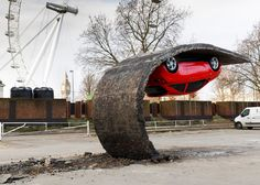 A section of tarmac appears to have been peeled back from the surface of a car park at London's Southbank Centre, suspending a car upside down in artist Alex Chinneck's latest illusionary installation.