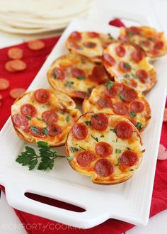 Easy Mini Tortilla Pizzas. They're mini and cute and delicious, and in this case, full of cheesy pizza goodness!