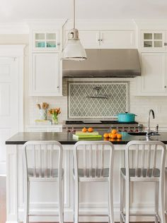 1006 Navy Counter Stools Sit At A White Kitchen Island Contrasted With A  Soapstone Countertop Finished With A Prep Sink And A Polished Nickel  Gooseneck ...
