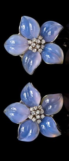 A Pair of White Gold, Chalcedony and Diamond Flower Earclips, consisting of 10 carved blue chalcedony petals surrounding central cluster stamens containing 22 round brilliant cut diamonds weighing approximately 0.88 carat total, hinged collapsible posts.
