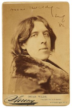 """Cabinet-size print of one of the 27 photographs that the leading New York photographer Napoleon Sarony took at the start of the writer's 1882 lecture tour of America. It is signed and dated '82. Wilde sports a long, heavy, fur-lined overcoat that he wore when he set sail for New York on Christmas Eve, 1881—without a word of the lectures on aestheticism that he was scheduled to deliver yet written—and which accompanied him everywhere. """"It was all over America with me … it knows me perfectly."""""""