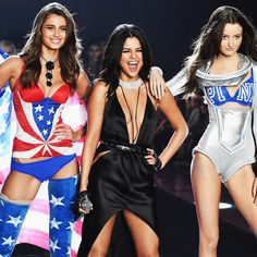 Taylor Hill from Illinois (L) and model Megan Puleri from Ohio (R) walk the runway while singer Selena Gomez performs during the 2015 Victoria's Secret Fashion Show